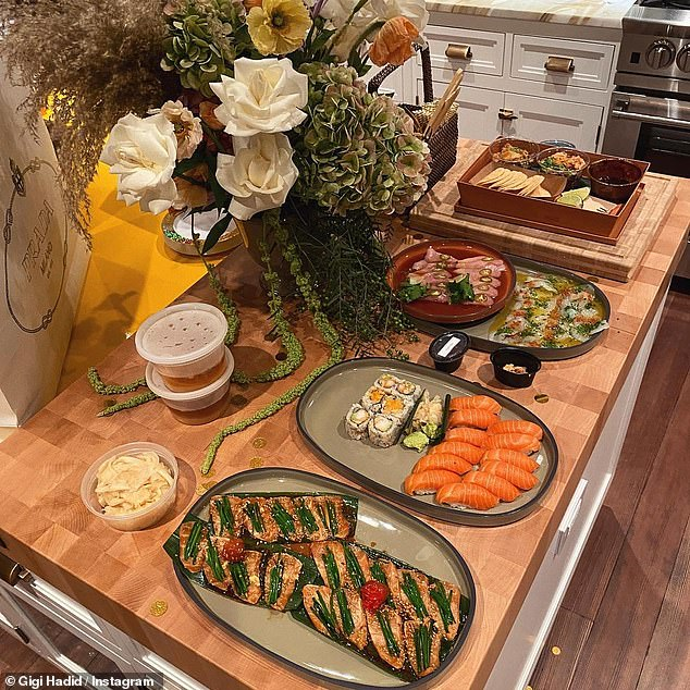 Yum: The second photo in the gallery showed a delicious spread of sushi and other appetizers, along with a stunning flower bouquet and white Prada shopping bag